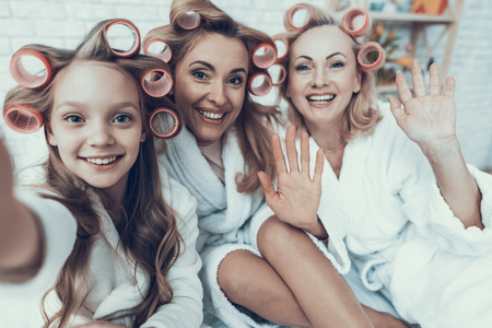 Photo pour Smiling Women in White Bathrobes Taking Selfie. Happy Family. Mother with Daughter. Smiling Women. Smiling Grandmother. White Sofa. Family after Bath. Women's Beauty Concept. Using Smartphone. - image libre de droit