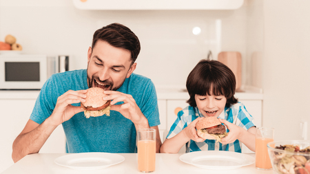 Foto per Smiling Son and Father Have Lunch in Kitchen. Boy in Shirt. Modern Kitchen. Sitting Boy. Boy with Spoon. Breakfast in Morning. White Table in Kitchen. Burger in Hands. Young Father. - Immagine Royalty Free