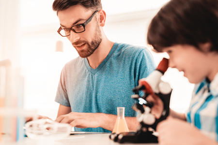Foto de Youn Bearded Father Teaching Son in Shirt at Home. Education at Home. Using Microscope. Studding Chemistry. White Table in Room. Sitting Boy. Young Father. Lesson at Home. Education Concept. - Imagen libre de derechos