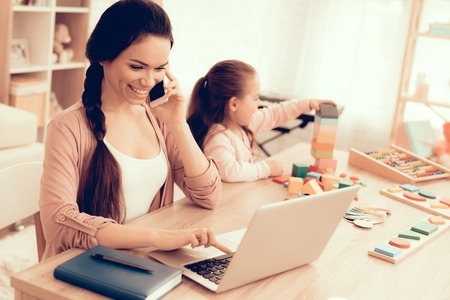 Foto de Mother Working at Home. Educational Games. Learning Child at Home. Child Development. Board Games for Children. Modern Learning for Children. Woman Working on Laptop. Girl Playing Educational Game. - Imagen libre de derechos
