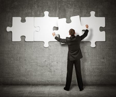 Foto de Businessman making a puzzle on the wall  - Imagen libre de derechos
