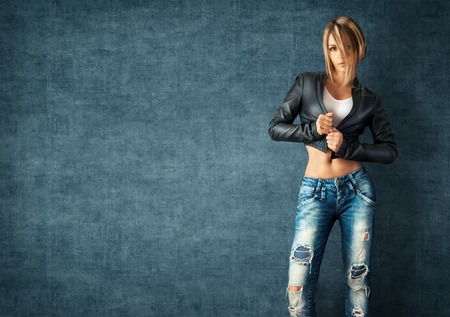 Photo for Sexy young woman in a trendy clothes on a grunge background - Royalty Free Image