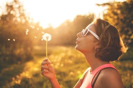 Foto de Happy young woman blowing on a dandelion in park  - Imagen libre de derechos