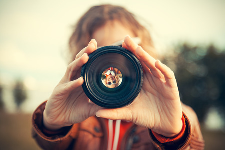 Photo pour Young woman looking through camera lens - image libre de droit