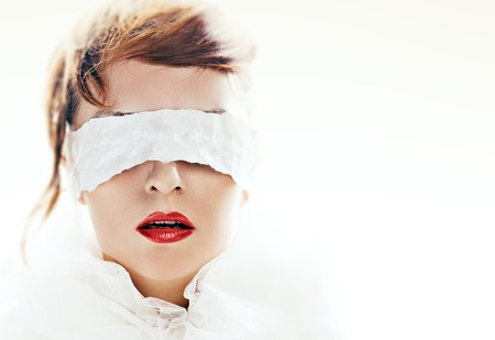Photo pour Portrait of attractive woman blindfolded with white paper ribbon - image libre de droit