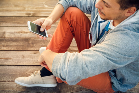 Foto de Young  hipster man using smart phone sitting on wooden boards - Imagen libre de derechos