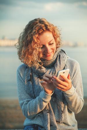 Photo pour Beautiful young  hipster woman using smart phone at beach - image libre de droit