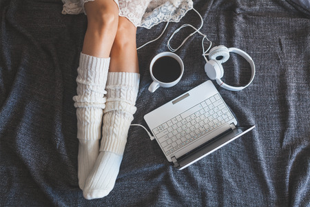 Photo for Soft photo of woman on the bed with notebook, headphones and cup of coffee, top view point - Royalty Free Image