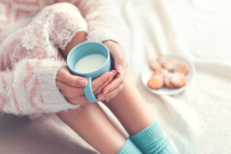 Photo pour Soft photo of woman on the bed with cup of milk in hands, top view point - image libre de droit