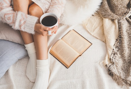 Photo pour Soft photo of woman on the bed with old book and cup of coffee in hands, top view point - image libre de droit