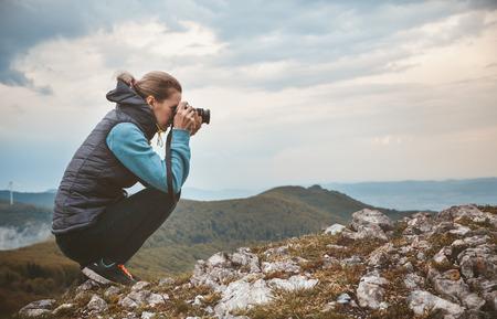 Photo pour Woman photographer is taking a picture of mountain landscape - image libre de droit