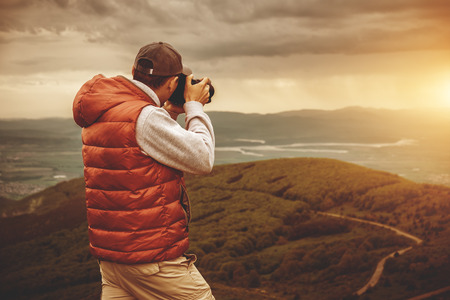 Photo pour Photographer is taking a picture of  sunset in mountains - image libre de droit