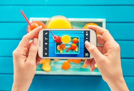 Photo pour woman taking picture of vintage tray with fruits on her smartphone. Top view - image libre de droit