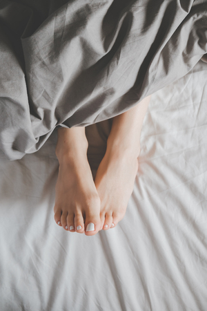 Photo for Soft photo of woman's feet under a blanket, top view point - Royalty Free Image