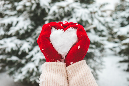 Foto de Woman in red gloves holds snow in hands in shape of heart. - Imagen libre de derechos