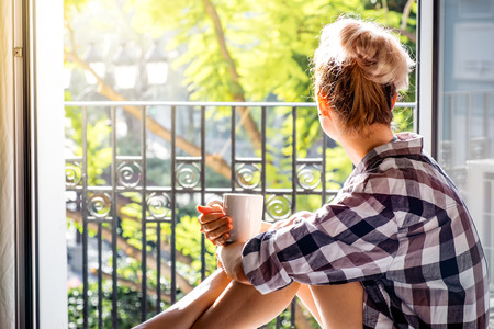 Foto de Young pretty woman  sitting at opened window drinking coffee and looking outside enjoys of rest - Imagen libre de derechos