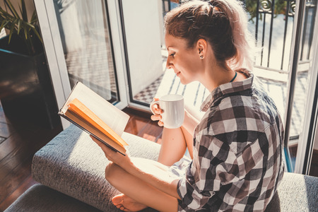 Photo pour Young pretty woman  sitting at opened window drinking coffee and reading a book enjoys of rest - image libre de droit