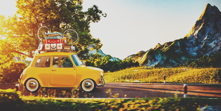 Photo pour Cute little retro car with suitcases and bicycle on top goes by wonderful countryside road at sunset - image libre de droit