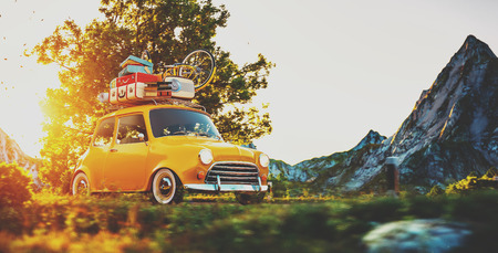 Foto de Cute little retro car with suitcases and bicycle on top goes by wonderful countryside road at sunset - Imagen libre de derechos