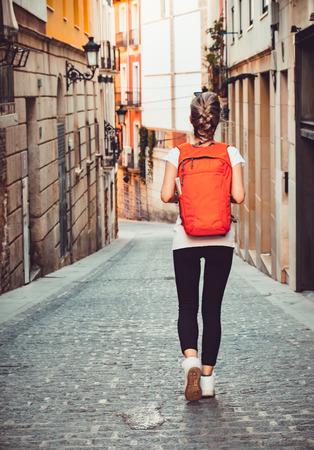 Foto de Tourist girl with backpack is walking by the street - Imagen libre de derechos