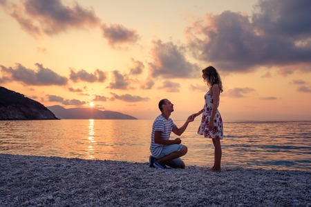 Photo pour Romantic marriage proposal on the beach at the seaside at sunset over the sea. Young couple in love - image libre de droit