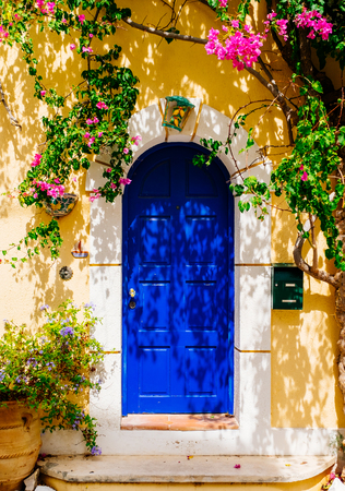 Photo pour Facade of traditional Greek building with beautiful pink flowers. Greece. Kefalonia - image libre de droit