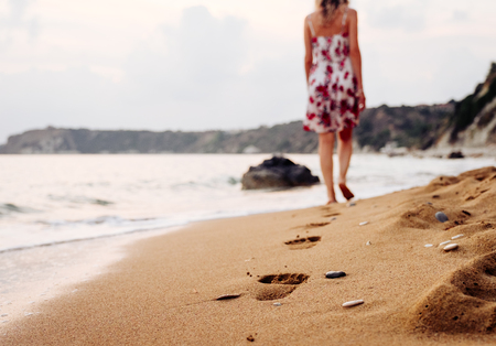 Foto de Beauty young woman in stylish dress walking barefoot by the beach leaving footprints in sand at sunset over the horizon. Travel and vacation concept. - Imagen libre de derechos