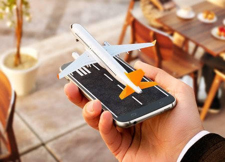 Foto de Smartphone application for online searching, buying and booking flights on the internet. Online check-in. Unusual 3D illustration of commercial airplane taking off on smartphone in hand - Imagen libre de derechos
