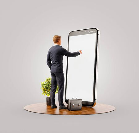 Photo pour Unusual 3d illustration of a young man standing in fron of big smartphone in office and touching smart phone screen. Smartphone apps concept. - image libre de droit