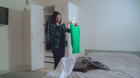 Photo pour Smiling caucasian brunette returned from the trip unpacking suitcase. Hanging clothes in a wardrobe. young caucasian tourist in apartment . - image libre de droit