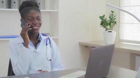 Photo for Doctor sitting at the working place in modern office using smartphone. Afro american cardiologist talking with boyfriend by mobile phone. Happy therapist with phonendoscope calling by cell in hospital. - Royalty Free Image