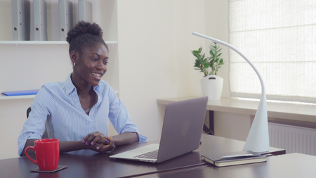 Foto für Enamored woman has video call with boyfriend in office. Young businesswoman with cute happy smile using laptop for calling. Girl sitting at the desk looking on monitor pc wearing casual dress clapping. - Lizenzfreies Bild