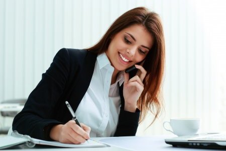 Photo pour Young happy businesswoman talking on the phone and writing notes in office - image libre de droit