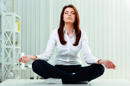 Photo pour Young beautiful businesswoman meditates on the table in office - image libre de droit