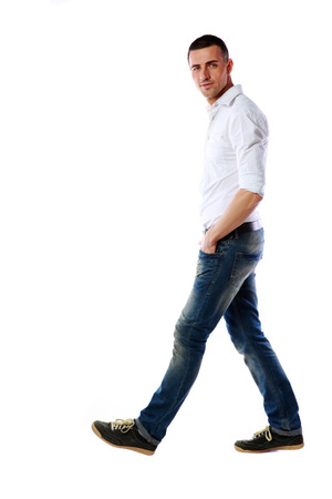Photo for Side view portrait of a casual man walking over white background - Royalty Free Image