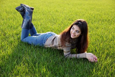 Photo pour Portrait of a happy woman lying on the lawn - image libre de droit