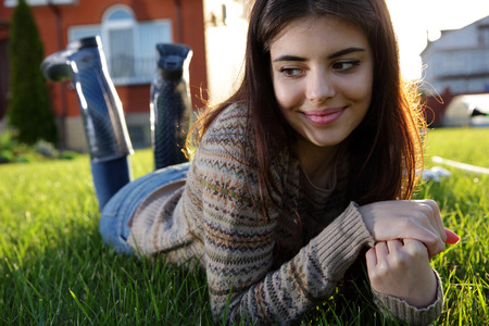 Photo pour Thoughtful woman lies on the lawn and looking away - image libre de droit