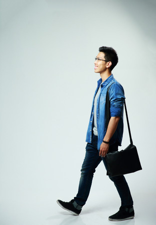 Photo for Studio shot of a young asian man walking on gray background - Royalty Free Image