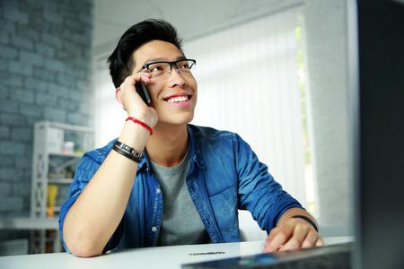 Foto de Young happy asian man talking on the phone at his workplace in office - Imagen libre de derechos