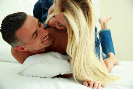Photo for Young love couple in bed, romantic scene in bedroom - Royalty Free Image