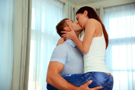 Foto de Portrait of a couple kissing at home - Imagen libre de derechos