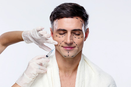 Foto de Man with closed eyes at plastic surgery with syringe in his face - Imagen libre de derechos