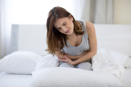 Photo for Young woman sitting on the bed with pain - Royalty Free Image
