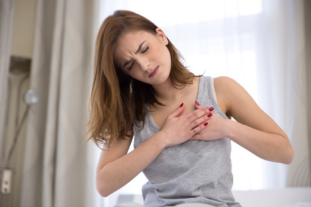 Foto de Young woman in pajamas having heart attack - Imagen libre de derechos