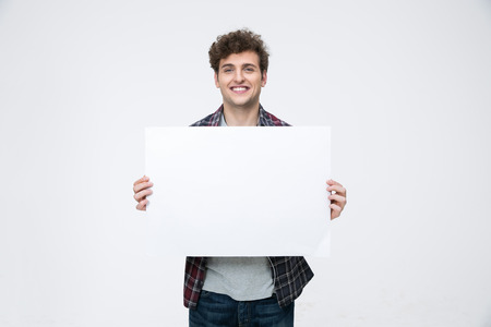 Photo pour Happy man with curly hair holding blank billboard - image libre de droit