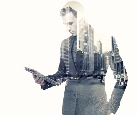 Foto de Double exposure of a businessman and a city using a tablet over white background - Imagen libre de derechos