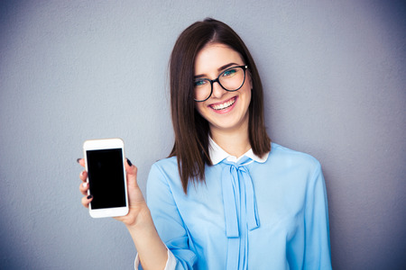 Photo pour Smiling businesswoman showing blank smartphone screen over gray background. Wearing in blue shirt and glasses. Looking at camera. - image libre de droit