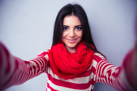 Photo pour Happy cute woman making selfie over gray background. Wearing in bright scarf and sweater. Looking at camera - image libre de droit