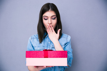 Surprised young woman standing with gift over gray background. Looking on gift. Covering mouth with her hand