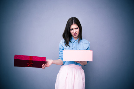 Photo for Dissatisfied woman opening gift over gray background - Royalty Free Image